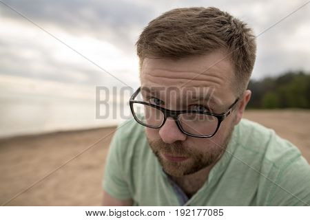 Bearded man in glasses looks questioningly blue eyes frowning on the sandy sea beach on a cloudy evening.