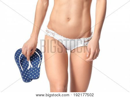 Beautiful young woman in bikini and with flip-flops on white background, closeup