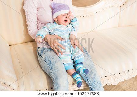 Tired newborn baby boy child rubbing eyes.