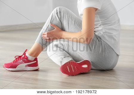 Young woman suffering from pain in leg while sitting on floor indoors