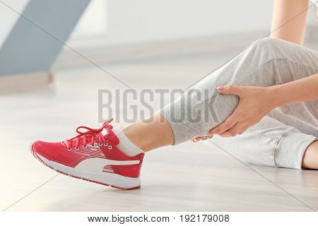 Young woman suffering from pain in leg while sitting on floor indoors, closeup