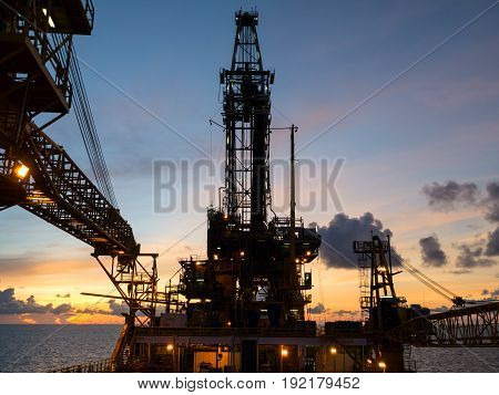 Derrick of Tender Assisted Drilling Oil Rig (Barge Oil Rig) on The Production Platform During Sunrise