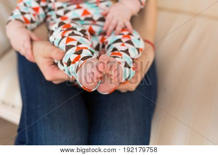 Baby foot in female hands, close-up. Cute little kid leg. Maternity, love, care, new life concept.