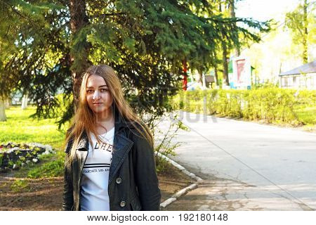 Surprise. A young pretty girl with light brown hair depicts different emotions. The girl is dressed in a black leather jacket and a white dress under her. She does this by walking in the spring park. Sunny spring evening.