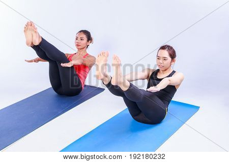 Two women practicing yoga in a health club gym training class session.
