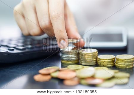 Female hand stack euro coins to shown concept of growing business and wealthy. Saving money concept