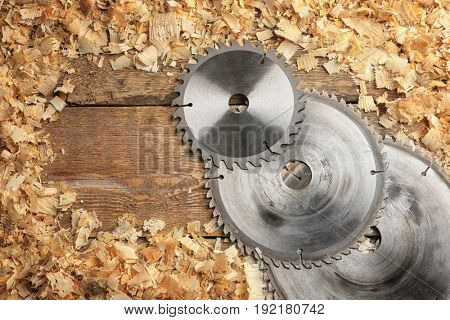 Composition with carpenter's circular-saw disks and saw dust on wooden background