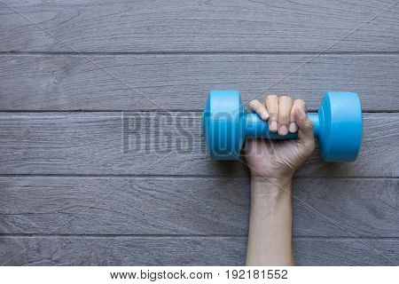 woman hand holding blue dumbbell on wood tale background