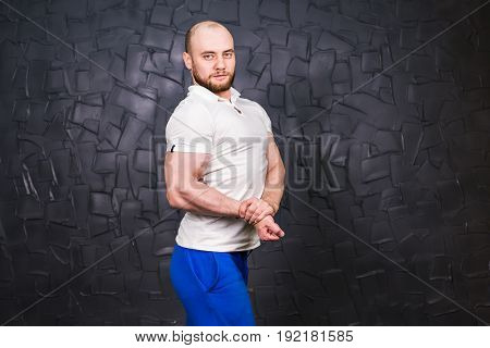 Young adult personal fitness trainer is posing on grey background