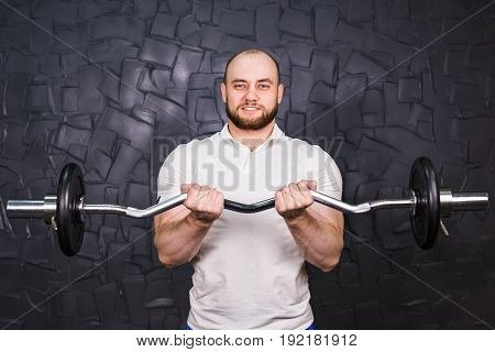 Muscular man working out in gym doing exercises, strong male with a barbell