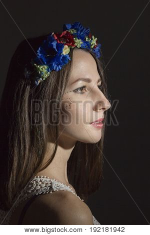 Portrait of a young woman in a wreath of flowers on a black background