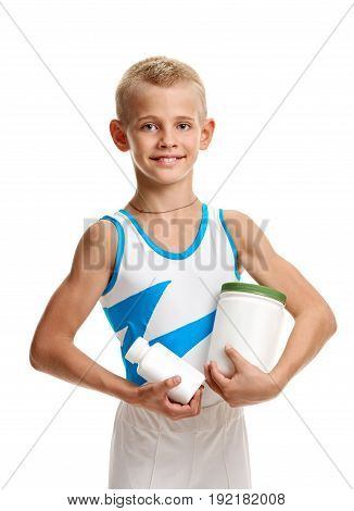 Young athletic sporty boy holding jars with vitamins
