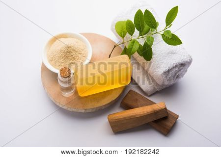 Ayurvedic handmade  Sandalwood both soap or chandan sabun with sandalwood sticks, ubtan or scrub or powder, oil and white towel, selective focus