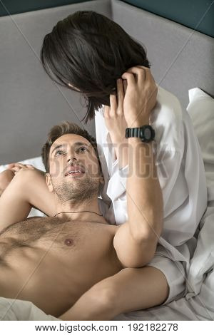 Handsome topless guy lies on his girlfriend's leg on the bed and looks at her face. She wears a white shirt. Closeup. Vertical.