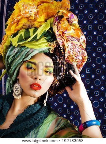 beauty bright woman with creative bright make up, many shawls on head like cuban, ethno look close up