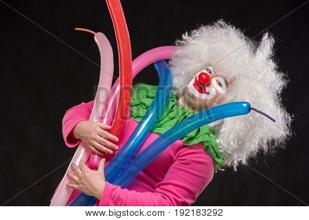 Funny clown with shaggy hair holding colorful balloons
