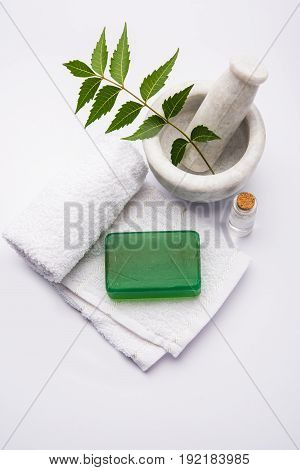 ayurvedic bath soap made up of Azadirachta indica or neem soap or sabun with mortar, neem leaves, neem oil and white towel, selective focus