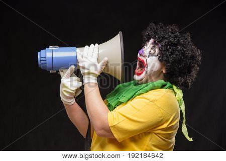 Scary evil clown shouting into a megaphone on a black background