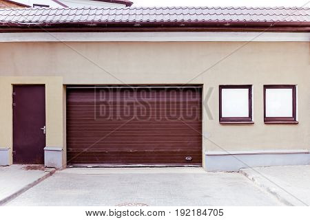 Closed Brown Corrugated Metal Garage Gate With Doorway And Windows On Plaster Wall