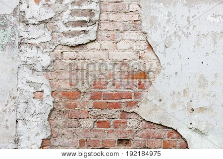 Aged brick wall with cracked plaster background