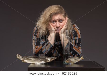 Lonely middle-aged woman drinks some vodka sadness alcohol and eating dried fish