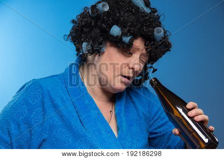 Lonely middle-aged woman drinking beer and vodka from a glass tumbler and eating pickles