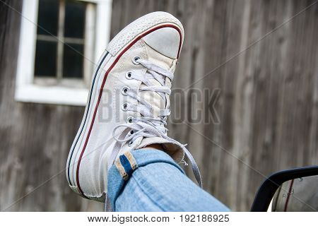 white sneaker hanging out of car window with old barn background