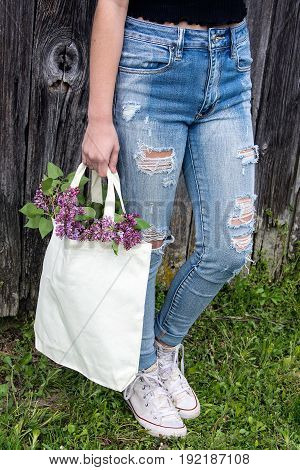 teenage girl wearing frayed blue jeans and carrying lilac bouquet in muslin sack by old barn