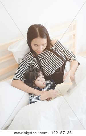 Happy loving family young asian mother reading a bed time story book to her daughter in bedroom.Photo design for family children and happy people concept