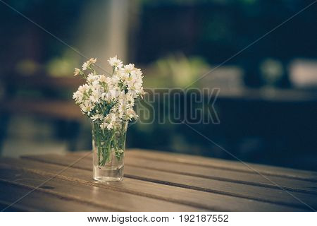 White flower on the wood table ; vintage colour tone