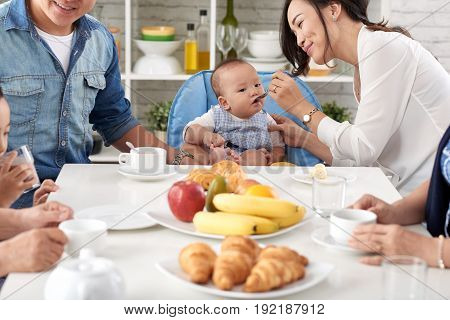 Portrait of young Asian woman spoon feeding cute baby boy at family dining table and smiling