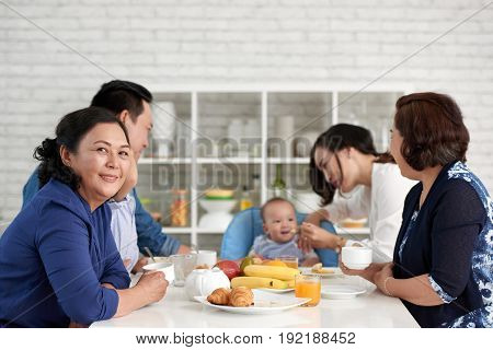 Portrait of mature Asian woman sitting at dining table with big family and smiling to camera