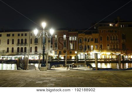lamp on a channel embankment at night in Venice, Italy