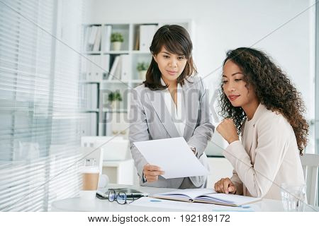 Beautiful Asian manager wearing gray suit sharing ideas with her colleague while gathered together in open plan office