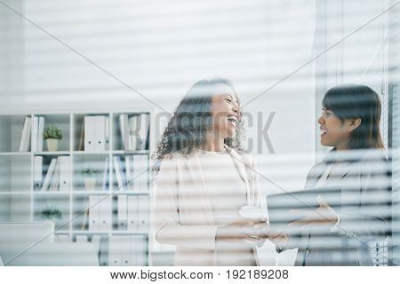 Waist-up portrait of laughing Asian coworkers standing at panoramic office window and chatting animatedly with each other during coffee break, view trough glass wall with blinds