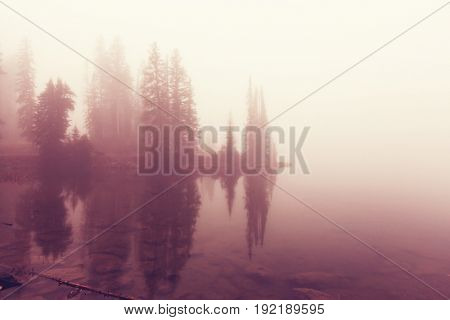 Misty mountain lake in the early serene morning in mountains.