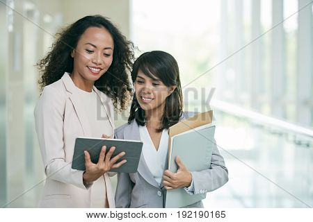 Waist-up portrait of attractive Asian coworkers standing in spacious office lobby and analyzing statistical data presented on screen of digital tablet