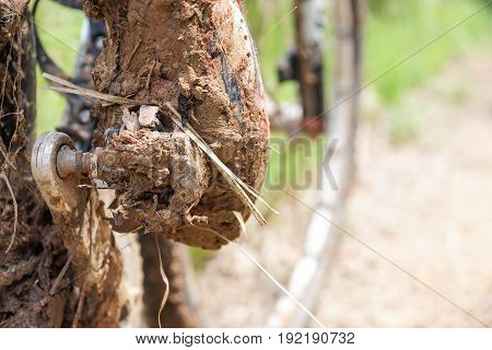 Mountain bike clipless shoes with mud and dirt stuck in the pedal / Cycling in wet and muddy condition concept