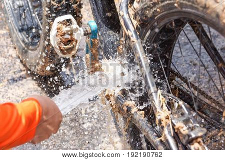 Cleaning a dirty mountain bike covered with mud and dirt