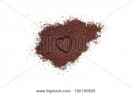 Pile of coffee grounds with a heart shaped indent isolated on white background