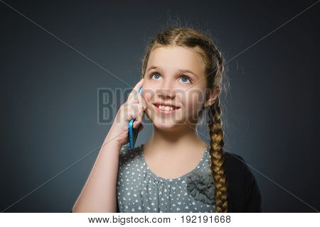 Cute girl with cell phone. isolated on gray.