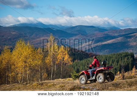 Guy Riding On An Atv On The Hilly Road On A Background Of Mountains, Forest And Blue Sky In The Autu