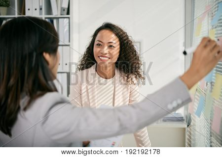 Unrecognizable businesswoman writing on sticky note while sharing ideas with her pretty Asian colleague with long curly hair