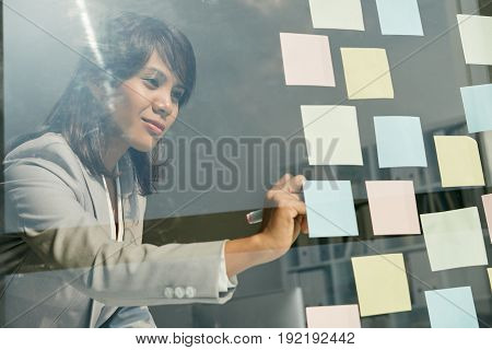Beautiful Asian white collar worker writing on sticky notes with marker while standing at panoramic window of modern office