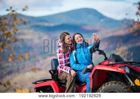Close-up Two Brunettes Women In Winter Jackets On Red Quad Bike Smiling And Makes Selfie On The Phon