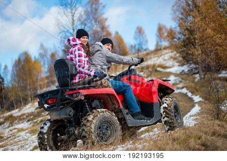 Girl Sitting Behind Man Hugging Him On Red Four-wheeler Atv And Looking To The Camera At Snowy Hill