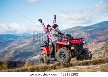 Guy Drive Atv Quad Bike, Girl Sitting Behind Him And Raised Her Hands Up On A Mountain Road On A Bac