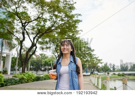 Smiling Vietnamese woman with plastic cup of iced tea in hand enjoying summer day and picturesque view on riverwalk, waist-up portrait