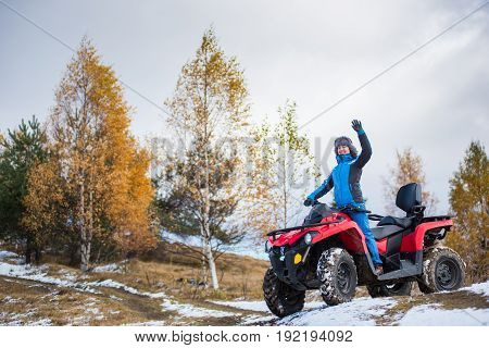 Happy Female Rider In Blue Winter Clothes Waving On A Red Quadbike Atv On Snow-covered Hill Against