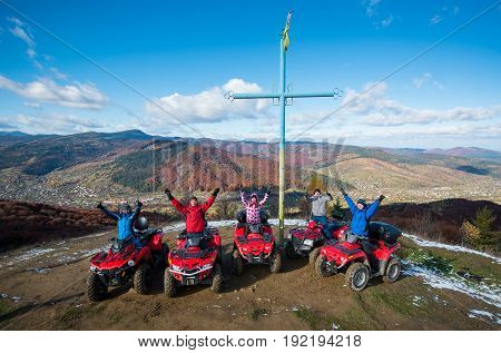 Group Of People With Raised Hands Up On Red Quad Bikes Near Cross With A Symbol Of Ukraine On Top Of